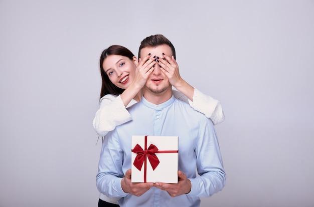 女性は彼氏に贈り物を与え、彼を抱擁します。