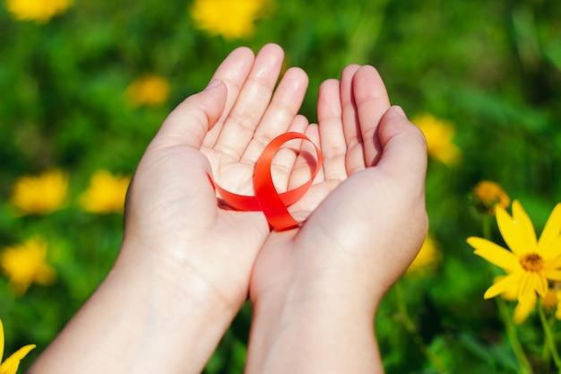女性の手は花の床に赤いリボンを与えます。