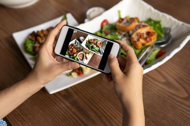 Рука женщины использует мобильный телефон, чтобы сфотографировать еду на обеденном столе в ресторане. фотография с помощью мобильных телефонов