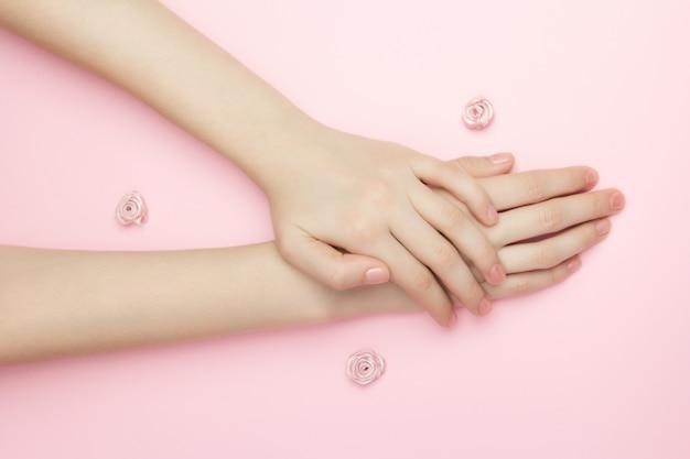 Руки женщины держат розовые цветы на розовой поверхности. тонкое запястье и натуральный маникюр. косметика для ухода за чувствительной кожей. натуральная косметика с лепестками, уход за руками против морщин.