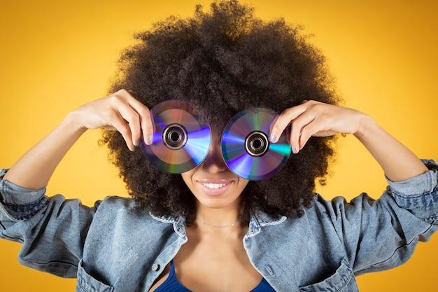 女性は、幸せな表情で、穴を通して見ている2つのデジタル多用途ディスクdvdを持っています