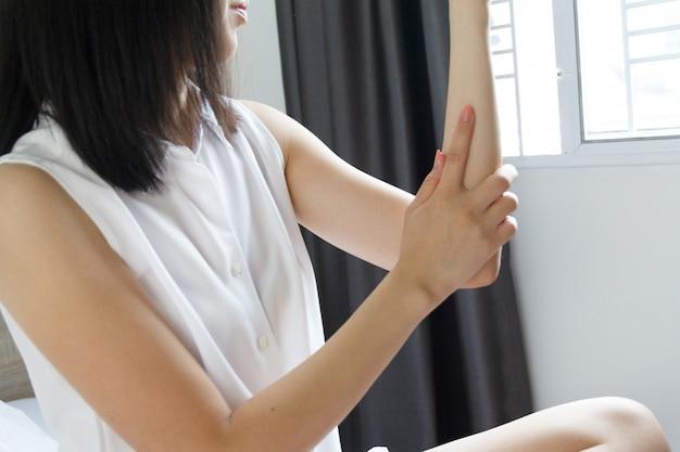 Женщина, страдающая от болей в локте в домашних условиях. концепция здравоохранения.