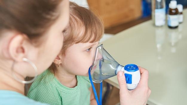 여자는 아이에게 마스크를 통해 호흡하는 데 도움이됩니다.