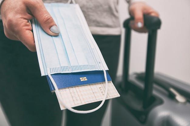 여자는 기차표와 의료 마스크가 달린 여권을 포스트 코 비드-19 시간 여행의 필수 요소로 가지고 있습니다.