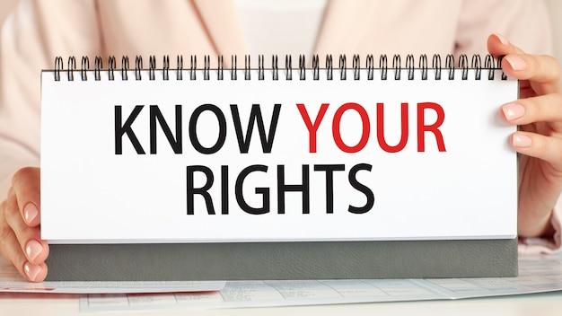 女性はあなたの権利を知っているというテキストで手で段ボールを持っています。黒い文字を書くテキスト。