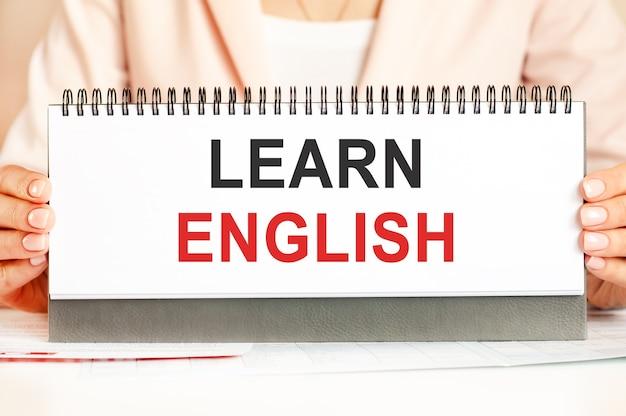 女性は、英語を学ぶというテキストが付いた手で段ボールを持っています。黒と赤の文字を書くテキスト。ビジネス、経済学、教育の概念。
