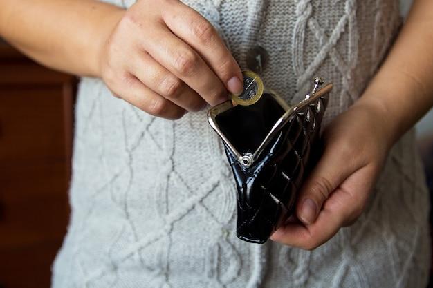Женщина держит монеты над старым пустым кошельком.