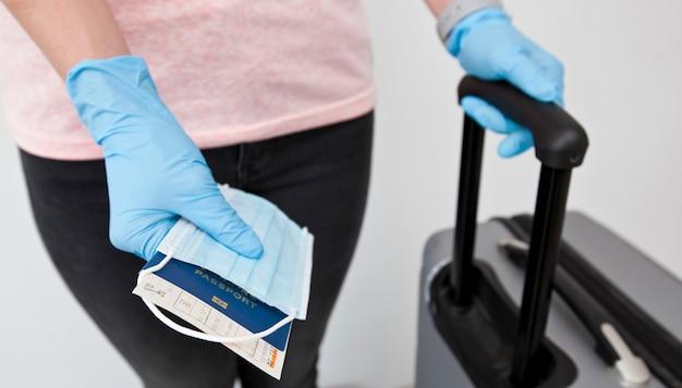 Женщина держит паспорт с билетом на поезд и медицинскую маску в руке, надев латексные перчатки, как неотъемлемую вещь в путешествии в постсоветское время.