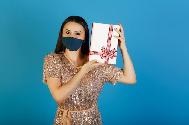 보호 마스크를 쓰고있는 베이지 색 드레스를 입은 여성이 코로나 바이러스 기간 동안 생일을 축하합니다.