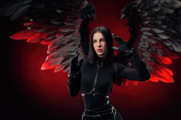 Женщина в черном боди с кожаными ремнями и черными крыльями на темно-красном фоне
