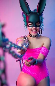 Женщина в ярко-розовом боди и маске кролика позирует на ярком фоне с цепочкой
