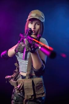Женщина в военной форме для страйкбола в жилете с американской автоматической винтовкой на темном фоне