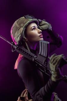 Женщина в военной форме страйкбола с американской автоматической винтовкой и шлемом на темном фоне