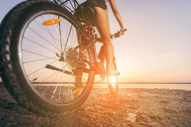 Женщина в разноцветном костюме сидит на велосипеде в пустынной местности у воды. концепция фитнеса. вид сзади и вид снизу. крупный план
