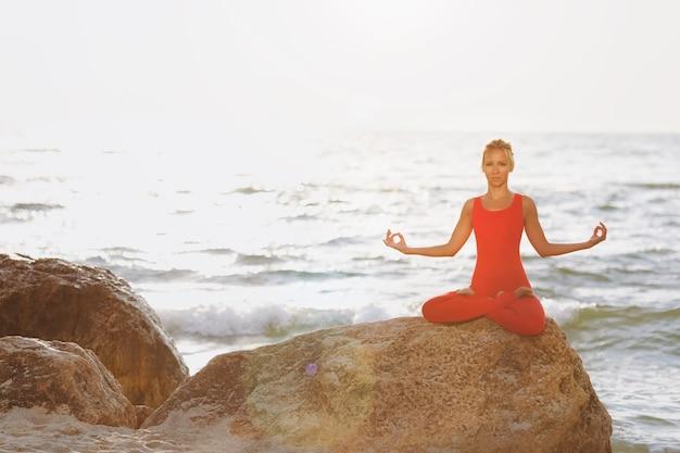 海の近くの日の出で石の上でヨガを練習している赤いスーツを着た女性