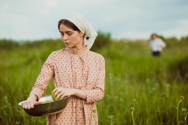 緑の牧草地に対してリンゴとハンカチの女性