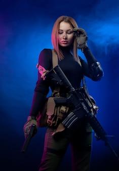Женщина в военной форме страйкбола с американской автоматической винтовкой и пистолетом на темном фоне