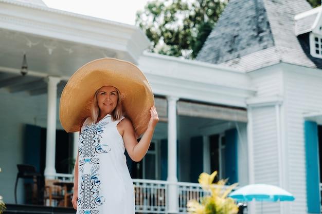 大きな帽子をかぶった女性は笑っています。大きな帽子と白いドレスを着た美しい少女がモーリシャス島の古い植民地時代の建物の外で微笑む
