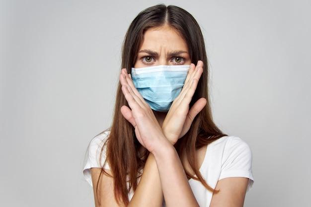 医療用マスクを着た女性が不機嫌な表情で彼女の前で腕を組んだ