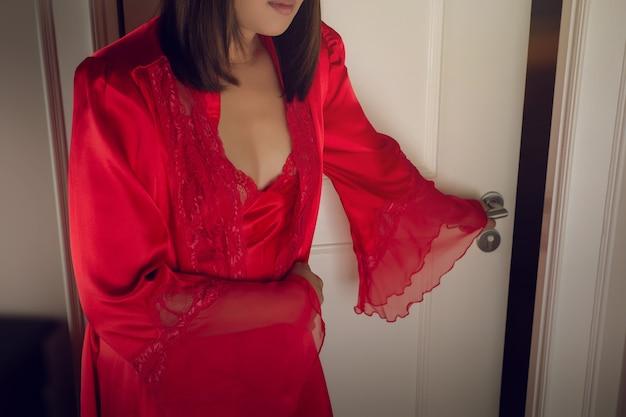 자정에 화장실 오른쪽 빨간 실크 잠옷을 입은 여성 아시아인들은 배가 아프다
