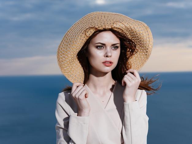 麦わら帽子と薄着の女性は海にいました。高品質の写真