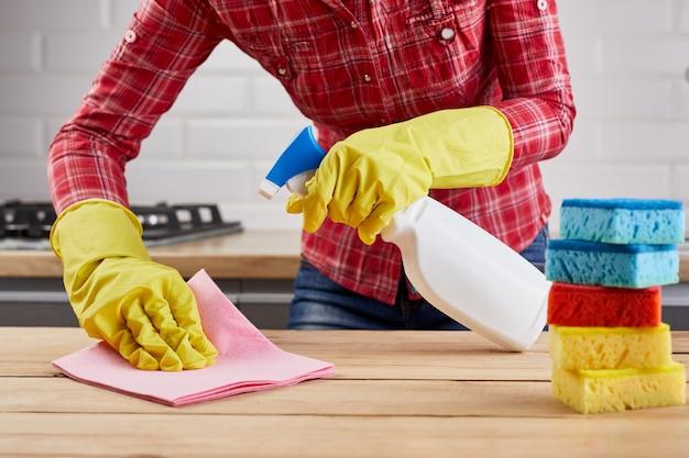 흰색 병 스프레이, 스폰지 및 걸레로 나무 테이블을 청소하는 노란색 보호 장갑에있는 여자