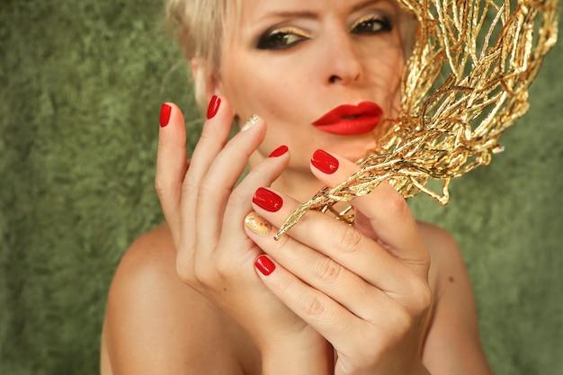 女性は短い赤い爪と唇で金髪です