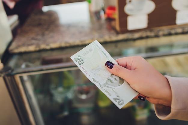 Женщина ведет счет банкноты турецких лир.