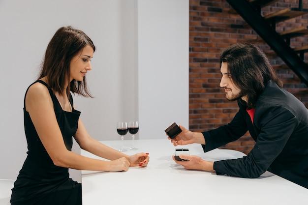 女性は喜んでいます。男性は指輪の入った箱を開けて、愛する女性にプロポーズをします。高品質の写真