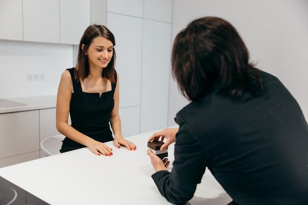 여자는 기뻐합니다. 남자는 반지가 달린 상자를 열어 사랑하는 여자에게 청혼을한다. 고품질 사진