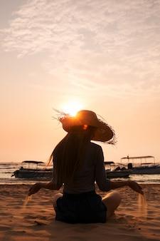 Женщина льет песок