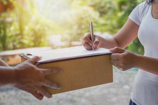 女性が配達員から渡された書類に署名している小包受け取り配達サービスのコンセプトを確認する