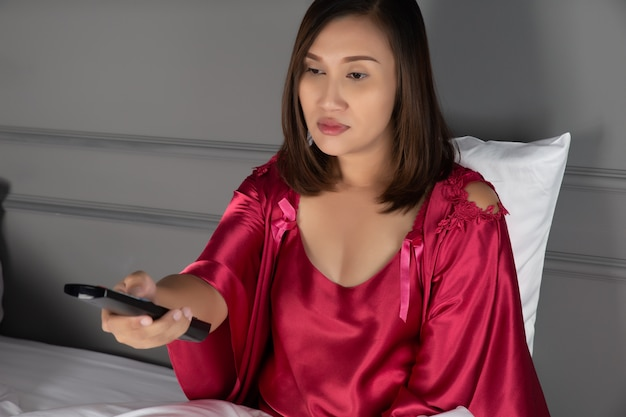 夜の寝室でテレビを見ている女性は眠い、アジアの女の子は不眠症のネグリジェとサテンのローブを着ている