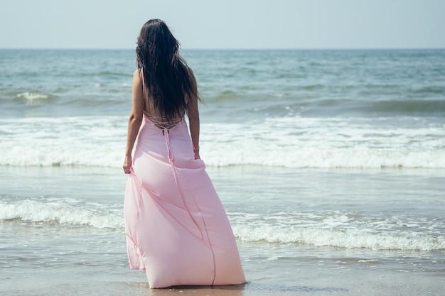 女性は海のそばに立っています