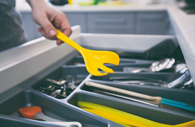 Женщина снимает кухонный инвентарь с полки с посудой.