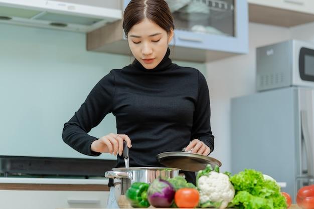 女性は彼女が調理しているスープを見ています