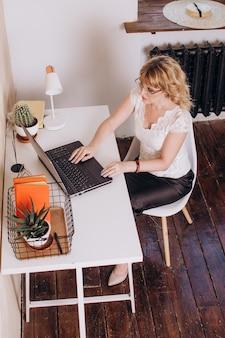 Женщина работает за ноутбуком. вид сверху.