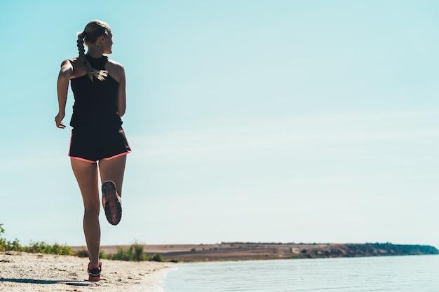 Женщина, бегущая трусцой вдоль морского побережья