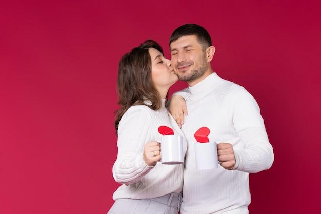 Женщина целует мужчину на красном фоне. молодые люди держат белые чашки чая.