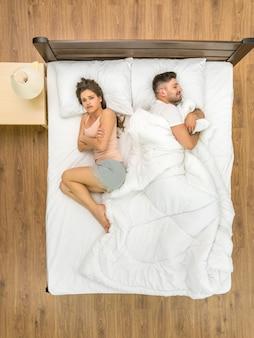 女性は毛布なしで男性の近くに横たわっていた。上から見る