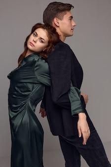 Женщина оперлась на спину мужчины на сером фоне, вид сбоку. фото высокого качества