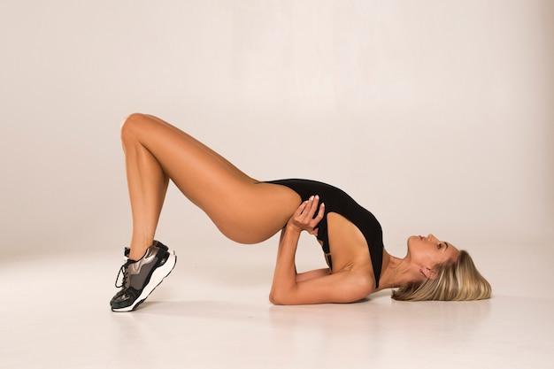 Женщина ложится на пол и сгибается в спине. у нее подтянутая спортивная фигура. Premium Фотографии