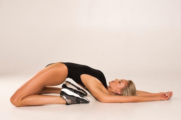 Женщина ложится на пол и сгибается в спине. она растягивает мышцы после интенсивной тренировки.