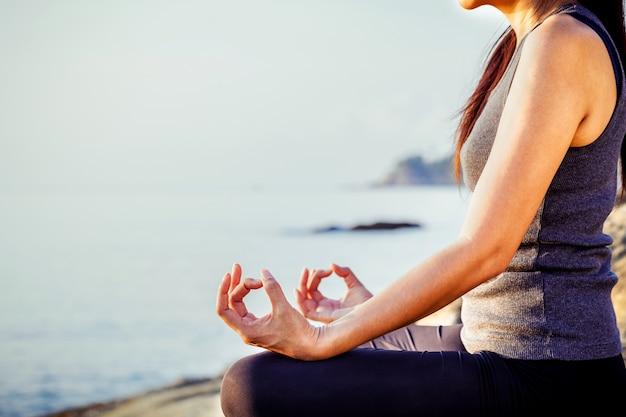 Женщина медитирует в позе йоги на тропическом пляже.