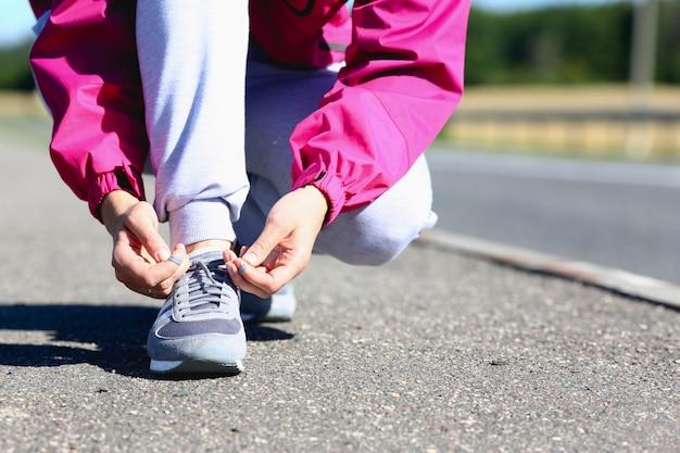 朝の女性はピンクのジャケットとグレーのパンツで走る