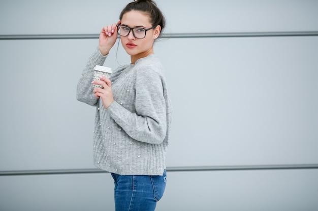 灰色の壁を背景に、長い黒髪と視力のための眼鏡をかけた女性