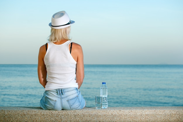 열대 국가에서 바다를 찾고 물병 해변에서 여자. 여행, 휴가 개념.