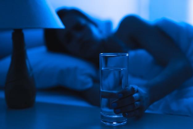 Женщина на кровати держит укол алкоголя. вечер ночное время