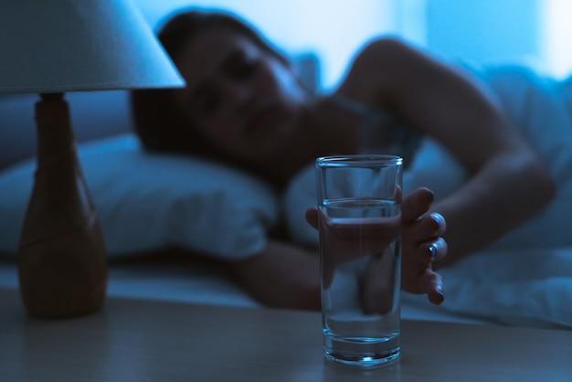 Женщина на кровати, держащая рюмку алкоголя