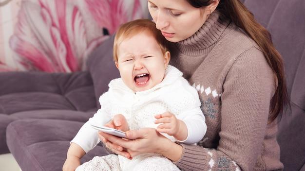 電話の女性は、泣いている子供を無視します。赤ちゃんが泣いています
